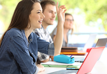 female student smiling and raising hand in class