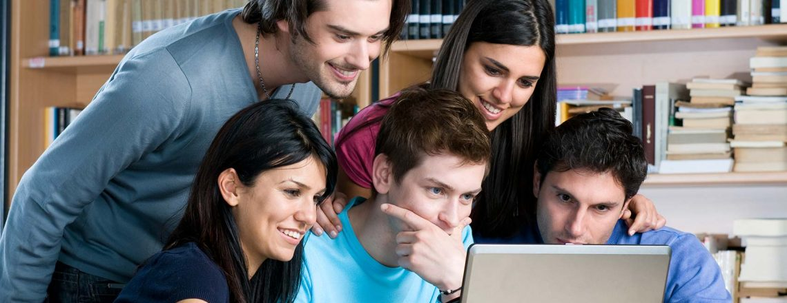 three male students and two female students look upon a single laptop