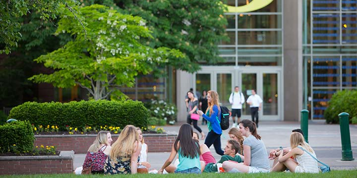 Group of learners sitting in the grass on campus in front of a building at the University of Oregon