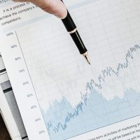 hand holding a pen pointing to a blue line graph on white paper