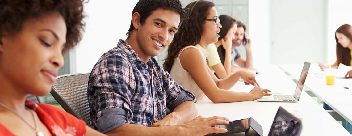one male student smiling and looking at the camera while sitting next to other students in the virtual classroom