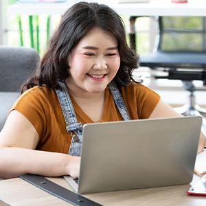 female wearing a hat programming on a laptop