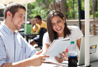 female and male student studying together outside with their laptop
