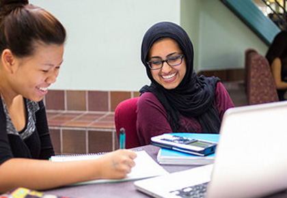 two female students studying together outside with a laptop