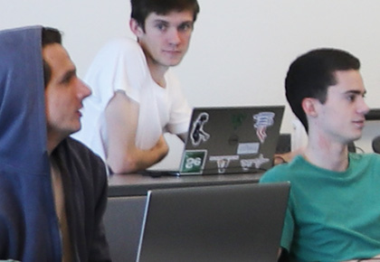 three male students sitting class with their laptops