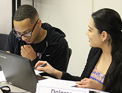 one male and one female student working at their desks