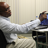 male student engaging in class conversation with his laptop on his desk