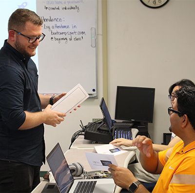 male professor talking to two male students at their desks with laptops